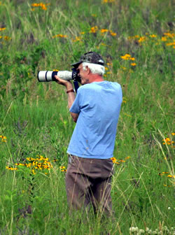 Dr. Johnsgard on one of his many photo-taking excursions on the prairie. (Linda Brown)