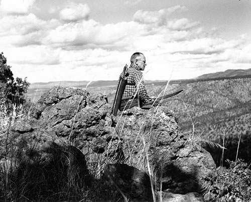 Aldo Leopold sitting on rimrock with a quiver and bow at Rio Gavilan, Mexico, 1938. (Starker Leopold/Aldo Leopold Foundation/www.aldoleopold.org)
