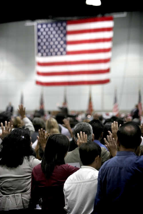 New immigrants taking the oath to become U.S. citizens at a public ceremony. (P_Wei/iStockPhoto.com)