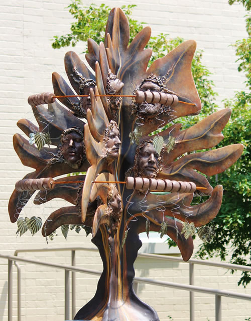 """Spirits of the Wind"" by artist, Janelle McKain of Gretna, Neb., temporarily installed in front of the Rowe Safety Complex on Central Avenue in Nebraska City. McKain's design incorporates dangling metal leafs hanging from steel rods and clay faces created using plaster casts of the faces of family and friends. (Tammy Partsch)"