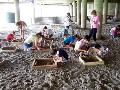Children and parents participate together in a Mock Archaeological Dig. Children simulate what real archaeologists do and unearth authentic artifacts they get to take home. (Remington Nature Center)
