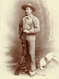 "James H. Cook, pictured here in 1886 after his cowboy days had ended, is wearing a buckskin suit and holding a Model 1873 Winchester rifle. Cook later owned the Agate Springs Ranch south of Harrison, Neb., near the site of today's Agate Fossil Beds National Monument. His autobiography, ""Fifty Years on the Old Frontier"" (1923), is a respected account of cowboy and ranch life. (NSHS)"