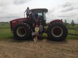 From top left: Faith, Thomas, Ward, Jacqueline, Matt, and Rosco the dog with the Hoculak's 2014 Versatile 450 tractor.(OCIA)