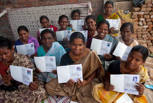 New landowners holding their land titles in India. (Deborah Espinosa)