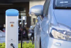An electric hybrid car charging up at an EV quick charging station. (martinplkang/iStockPhoto)