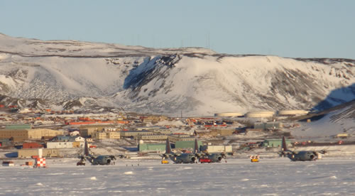McMurdo station supports around 1,000 people at a time during the summer, including this year's 56 ANDRILL scientists at the Crary Science and Engineering Center. That number is reduced to about 125 during the long winter. The aircraft visible in the foreground are LC103 ski-equipped Hercules planes, the workhorse of the Antarctic air  operations for the U.S. Antarctic Program. (Photo by David Harwood)